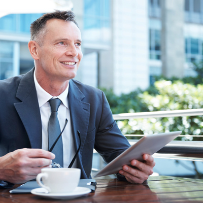 Businessman smiling and on i-pad whilst drinking a coffee